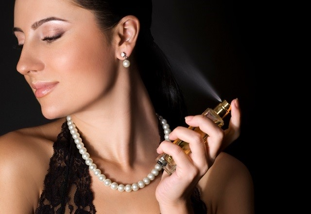 Elegant woman with perfume on black