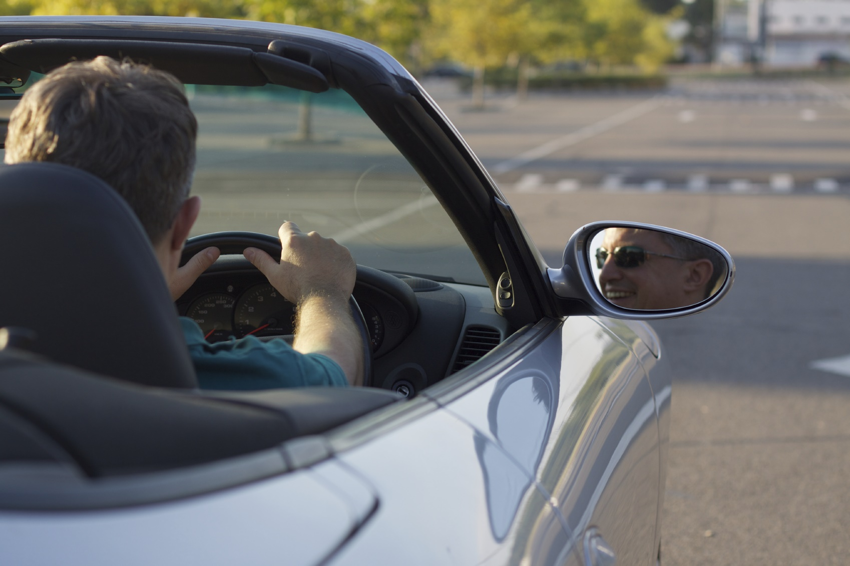Man driving a convertible sports car. Smiling and enjoying the moment.
