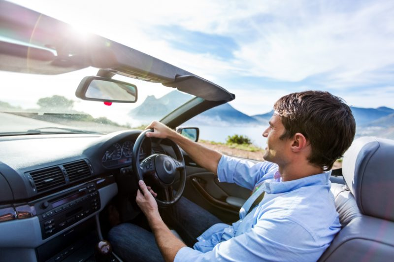 Man Driving Convertible Car On Road Trip