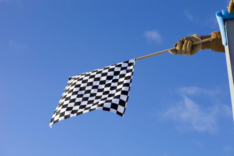 Checkered Auto Race Flag against a Clear Blue Sky
