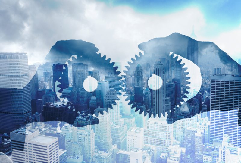 Multiple Exposure Of Businesspeople Interlocking Gears In Front OF City