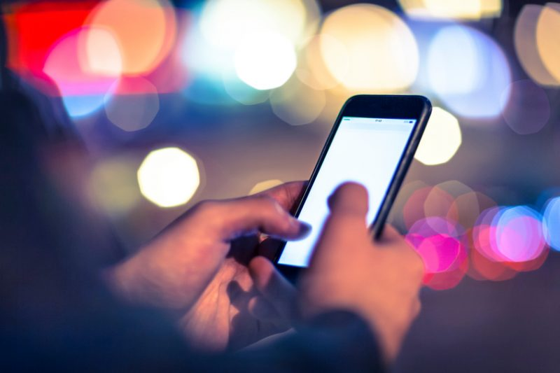 Using smart phone at nighttime outdoors