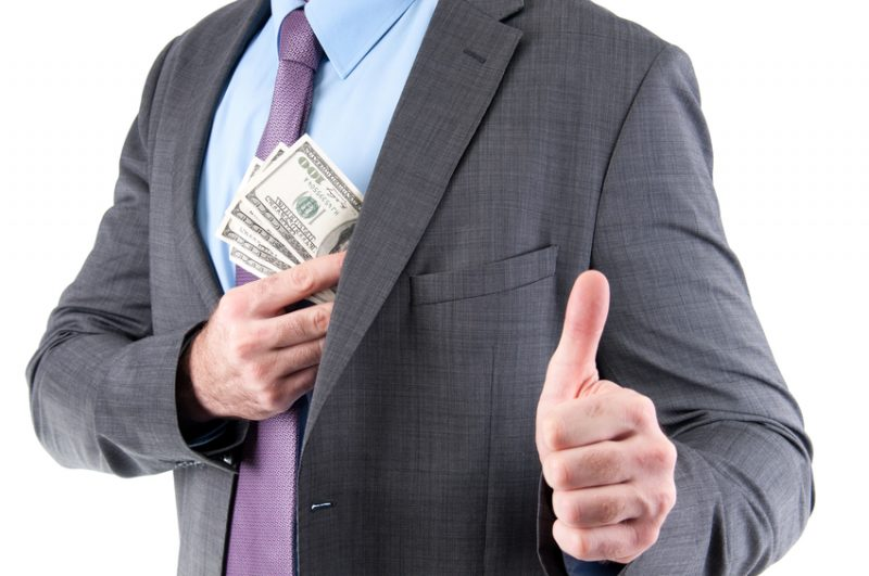 Dollars in a pocket of corrupted businessman showing thumb up