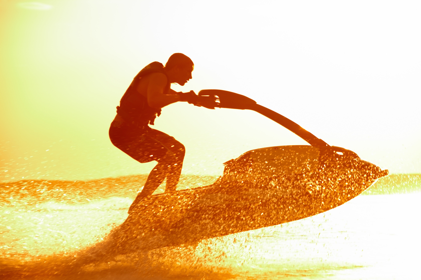 strong man jumps on the jetski above the water at sunset
