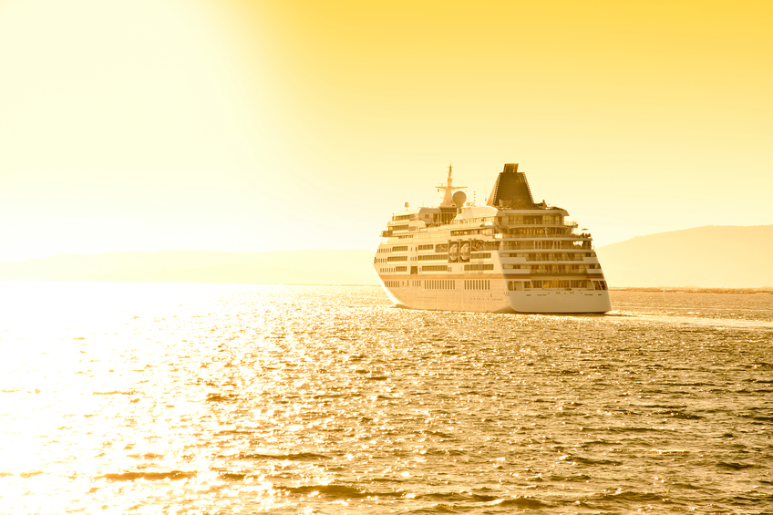 a cruise ship sailing to the sun at twilight