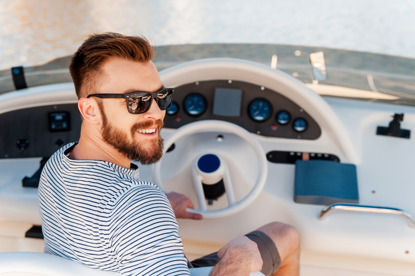 Smiling young man holding hand on steering wheel while driving yacht