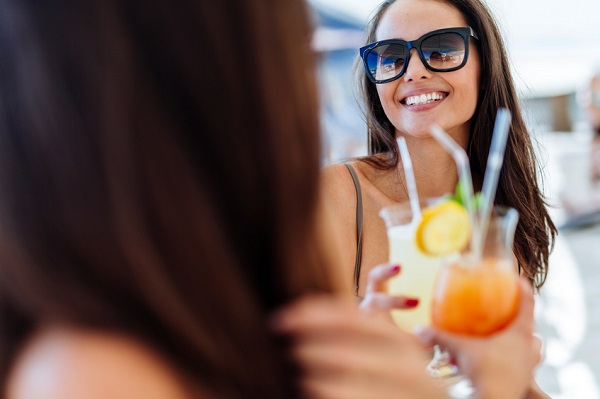 Cheerful female friends drinking cocktails in summer and smiling