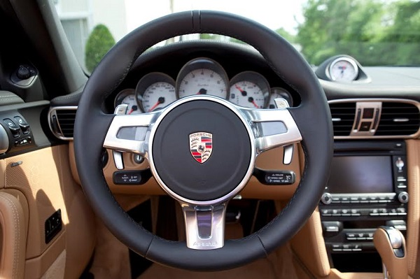 """Nashville, Tennessee, USA - June, 11th 2010: A 997 generation Porsche 911 Turbo convertible's steering wheel with Porsche logo, dashboard and radio console, photographed with the top down outside."""