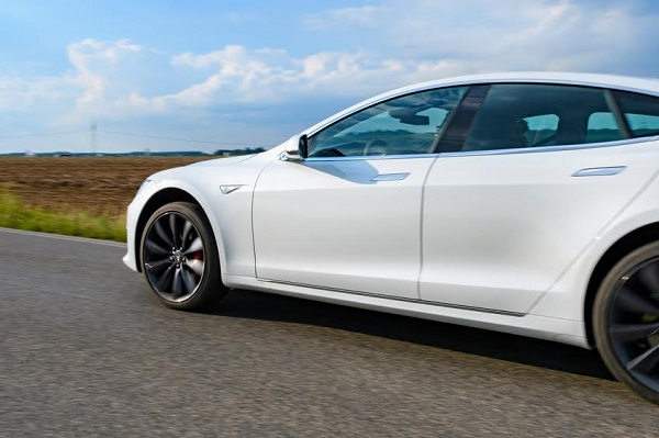 Jüchen, Germany - August 5, 2016: White Tesla Model S full electric luxury car driving past on a country road. The Tesla Model S is a full-sized plug-in electric five-door, luxury liftback, produced by the American automotive company Tesla Motors.