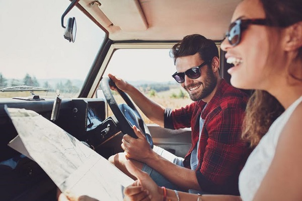 Happy young couple with a map in the car. Smiling man and woman using map on roadtrip.