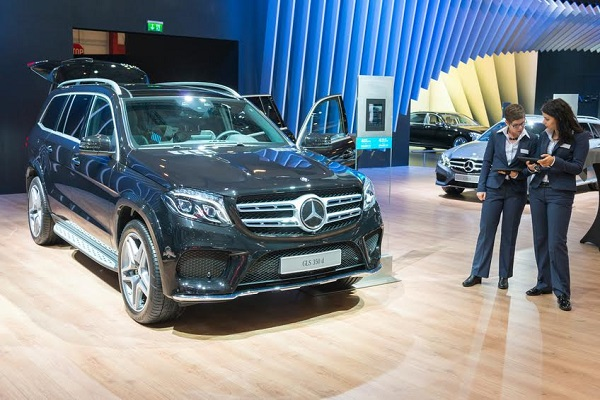 Brussels, Belgium - Januari 12, 2016: Mercedes-Benz GLS luxury SUV front view. This GLS 350 d 4MATIC is fitted with a V6 diesel engine and a nine-speed 9G-TRONIC automatic transmission. Two sales women are standing in front of the car. The car is on display during the 2016 Brussels Motor Show. The car is displayed on a motor show stand, with lights reflecting off of the body. There are people looking around and other cars on display in the background.