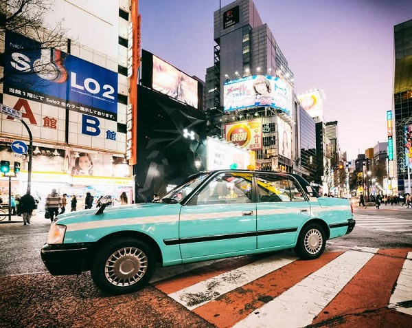 A nighttime street scene in the Shibuya area of Tokyo, Japan. A taxi sits on a zebra crossing, waiting for passengers.