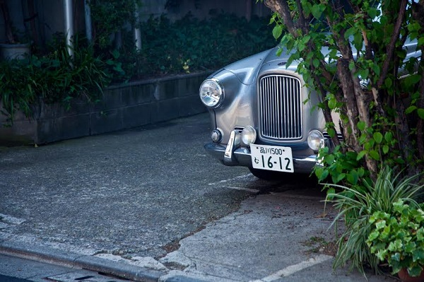 Tokyo,Japan,28th April 2012 : Retro style car parked off the street in the town , front of the ca visible , obscured by the plant