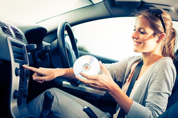 Young female driver playing music in the car, changing a CD in a player