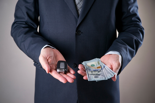 Car key and hundred-dollar bills in hands of a businessman