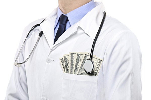 A portrait of a male doctor with  money in his pocket isolated on white background