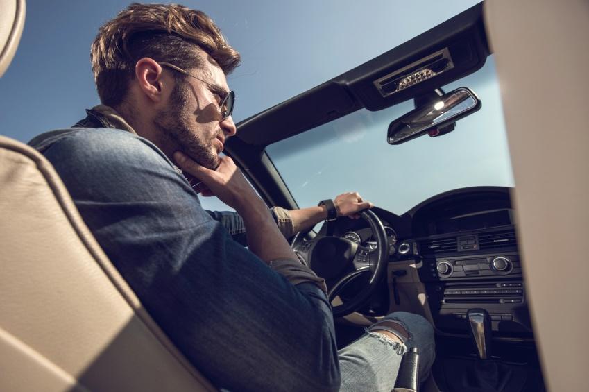 Below view of a pensive man driving a convertible car.