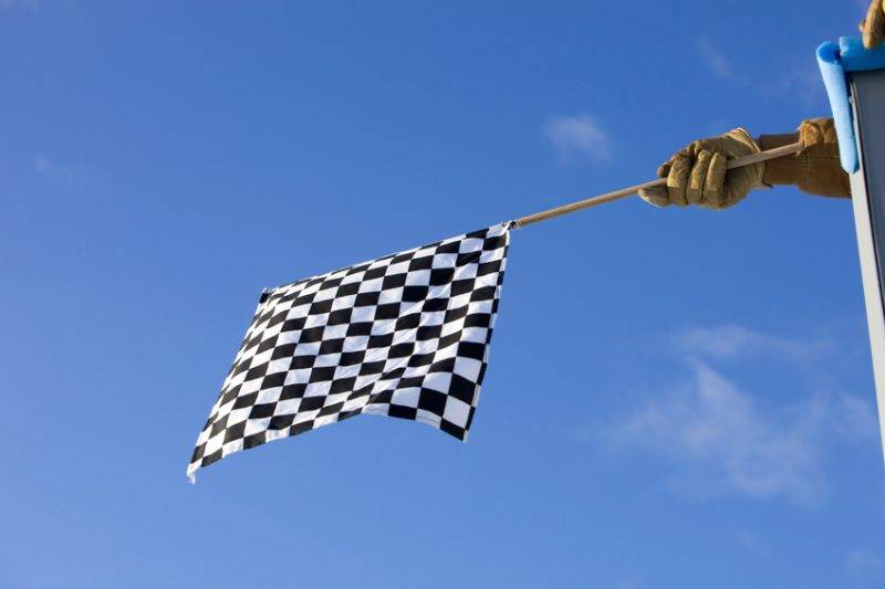 Checkered Auto Race Flag against a Clear Blue Sky