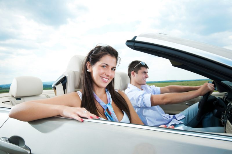 Attractive couple driving in their Convertible car.