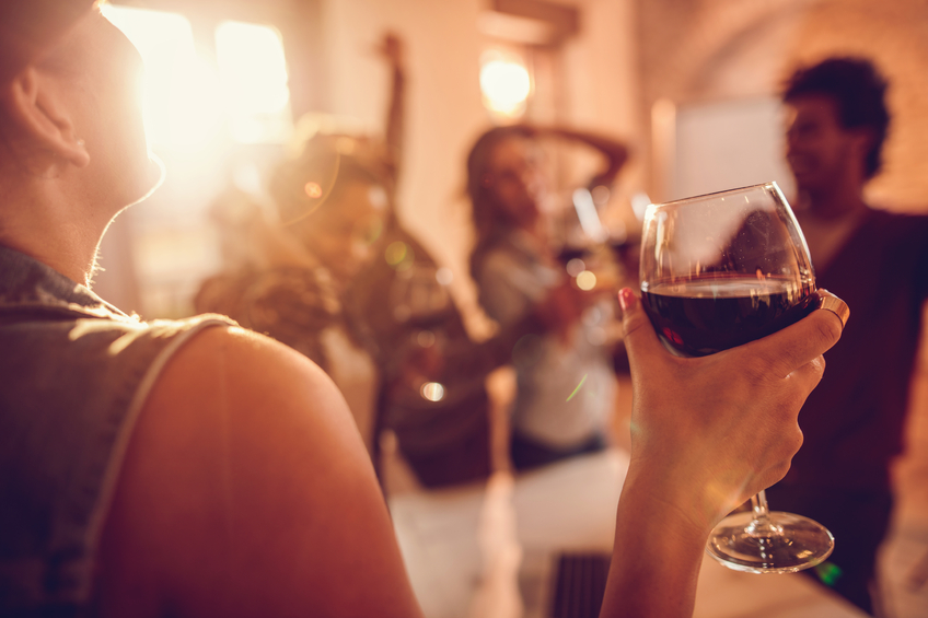 Close up of a businesswoman enjoying in a glass of red wine while being at office party with her colleagues.