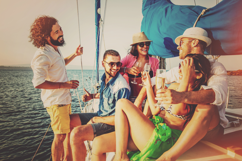 Young people having party on a yacht, with champagne.