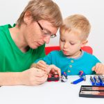 Father teaching son how to repair toy train. Learning and early education concept