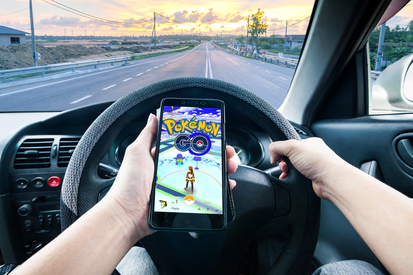 """California, United States, - July 16, 2016: A man is dangerously playing Pokemon Go while driving and tried to catch the """"Pocket Monster"""". Pokémon Go is a free-to-play location based augmented reality mobile game developed by Niantic and published by The Pokémon Company as part of the Pokémon franchise."""