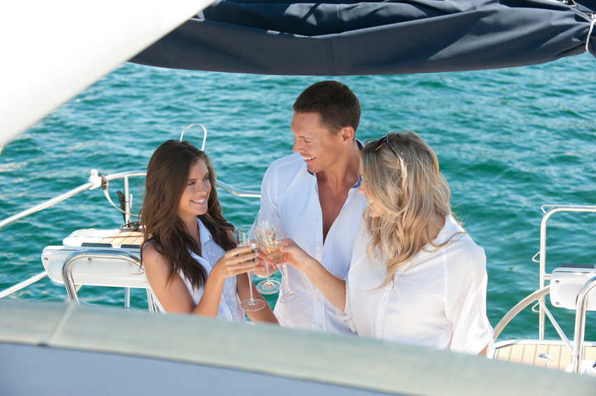 Friends laughing and relaxing on sailing boat with champagne