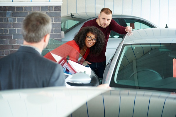 A young couple are looking at  cars in a car showrooms . A salesman is explaining about the car whilst the young couple listen and look at a car .