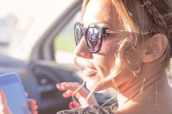 young beautiful woman uses phone in a car