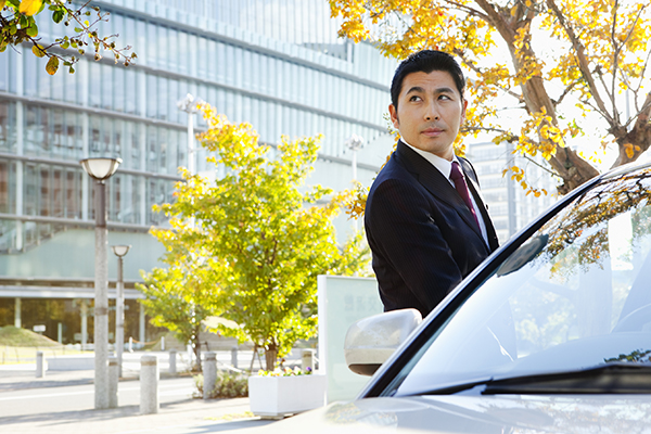 Businessman boards his car.